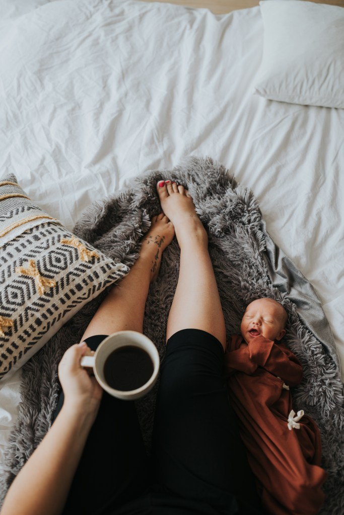 Mother in bed with baby drinking coffee