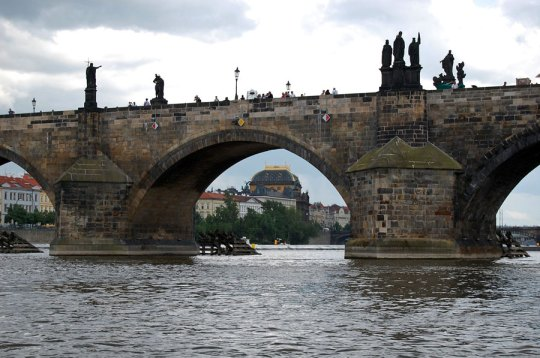 Charles Bridge viewed from Vltava river; National Theater in the background