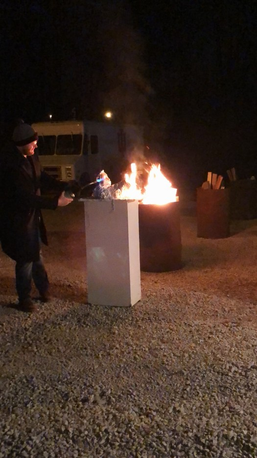 A man blow torching an abandoned piece of art.