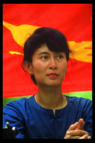 Aung San Suu Kyi in front of an NLD Flag