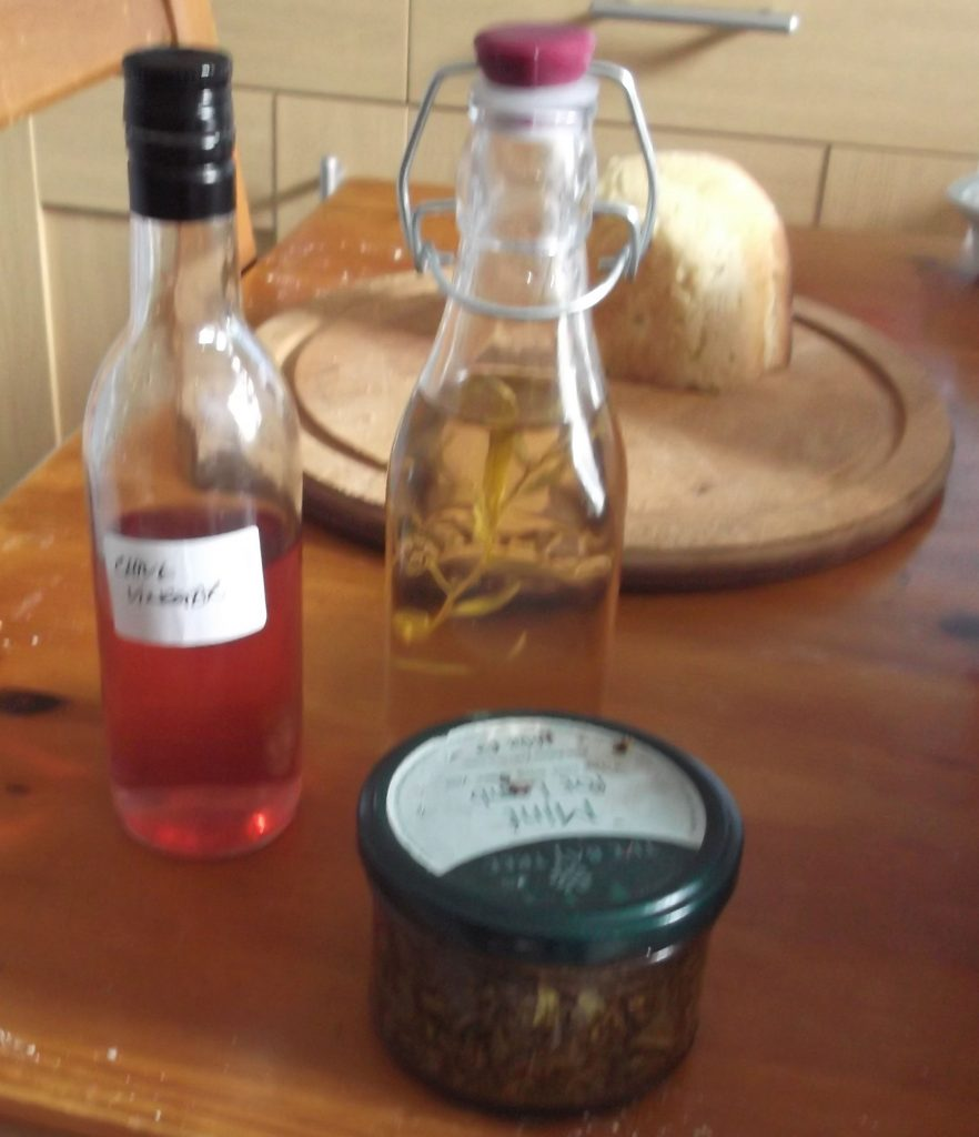 bottles of tarragon and chive flower vinegar, jar of mint sauce
