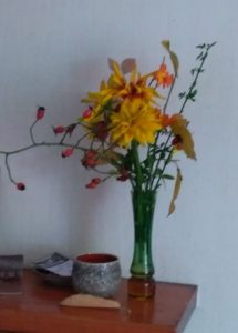 a vase of autumn flowers and berries