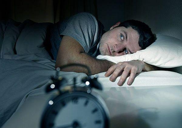 Man in bed lying awake at night.