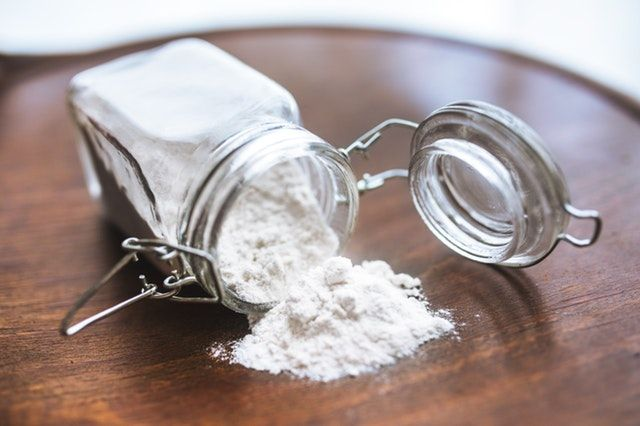 Jar of flour spilled on counter.