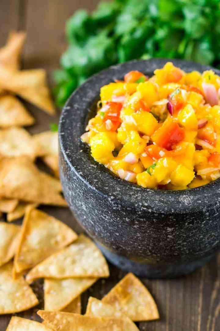 A bowl of tropical pico de gallo with cilantro and homemade chips.