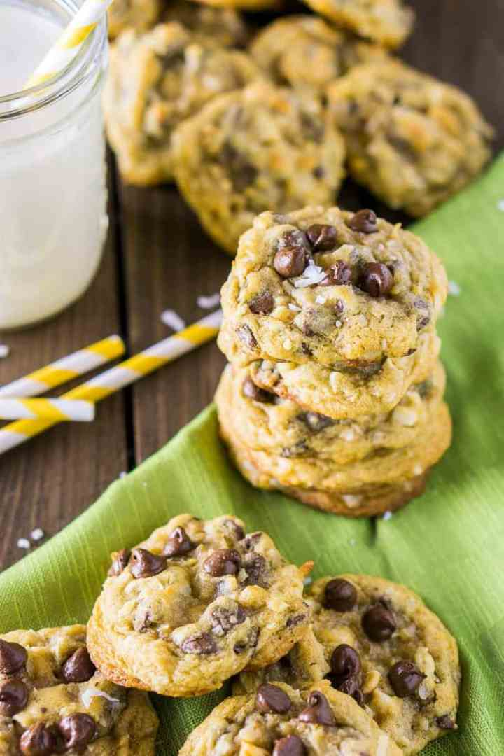 A stack of chocolate chip-coconut-macadamia nut cookies with a straw and milk.