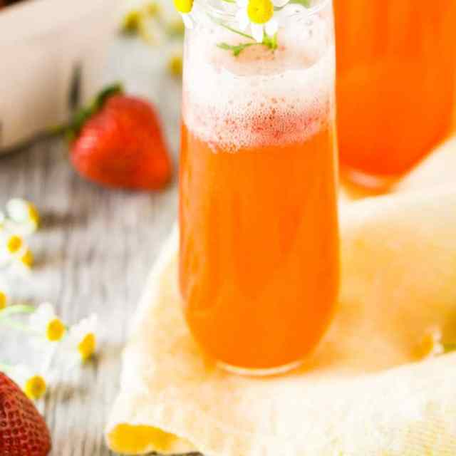 Two roasted strawberry Aperol spritzes with flowers on a yellow napkin.