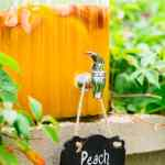 A drink dispenser outside filled with peach sangria.