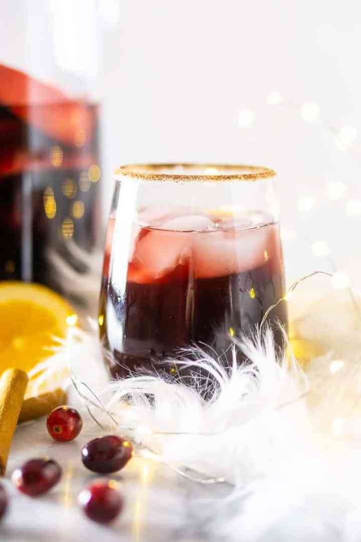 A front view of holiday sangria with pitcher in the background.