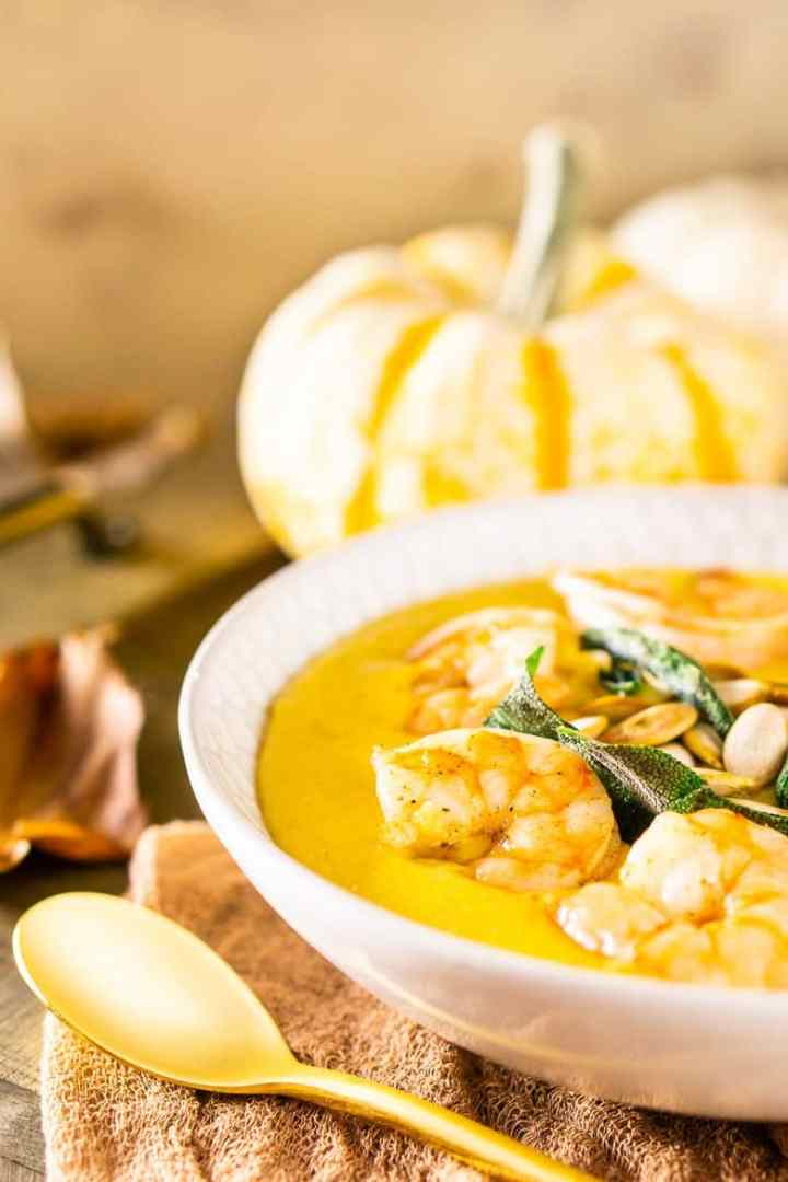 A close-up of pumpkin polenta with brown butter shrimp, pumpkin seeds and fried sage with pumpkins and fall leaves as decor.