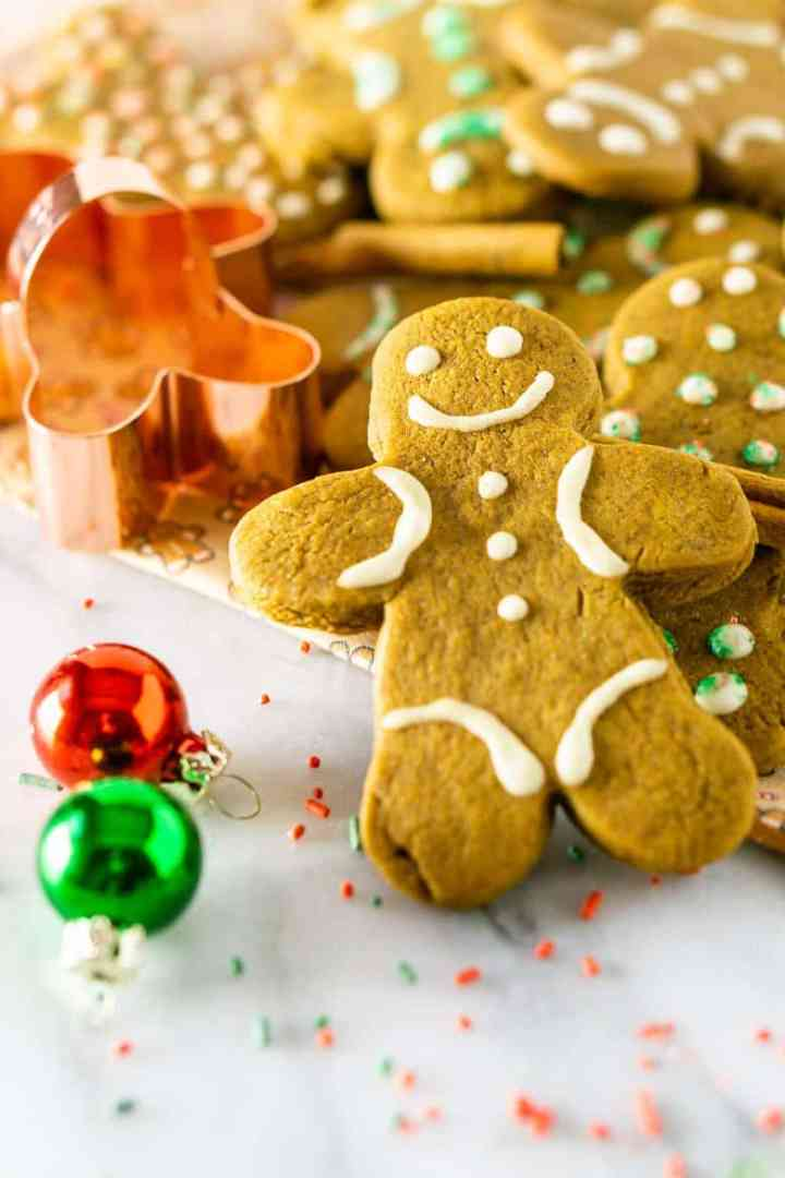 A pile of gingerbread men cookies with a cookie cutter.