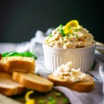 A bowl of herbed smoked trout spread with crostini.