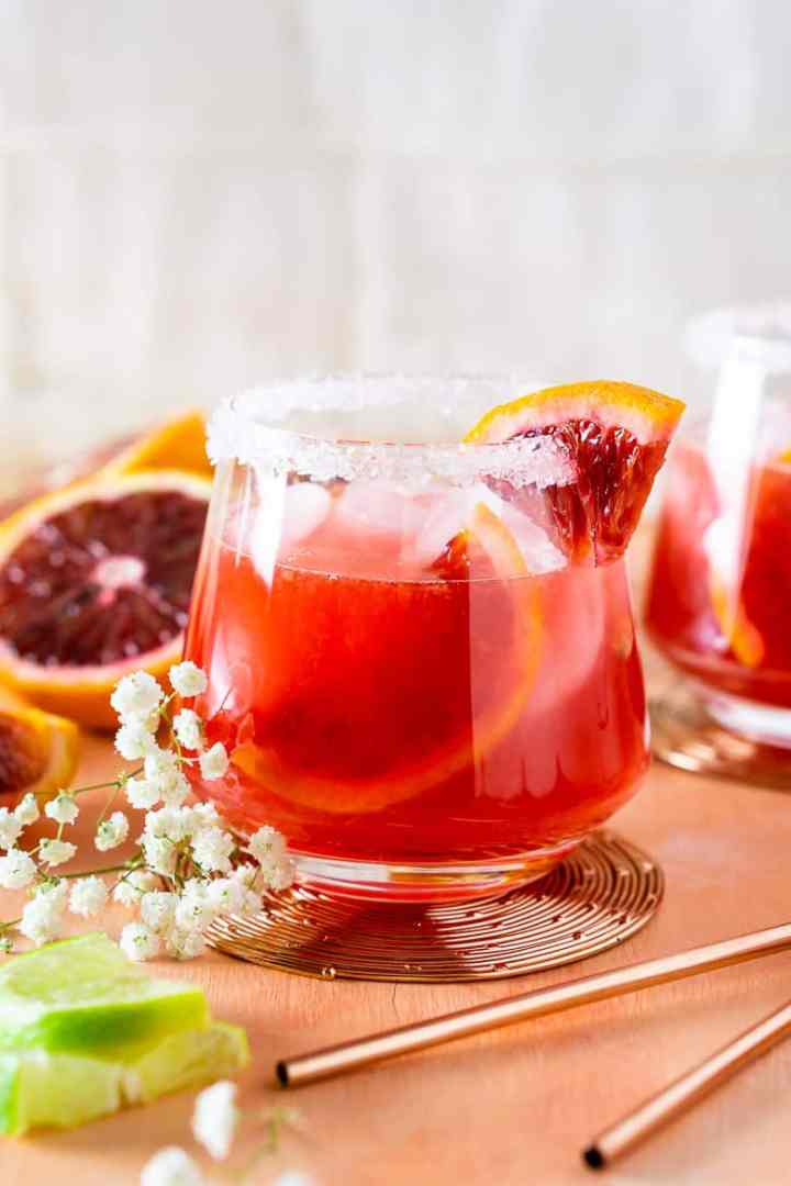 A front view of a blood orange margarita with white flowers.