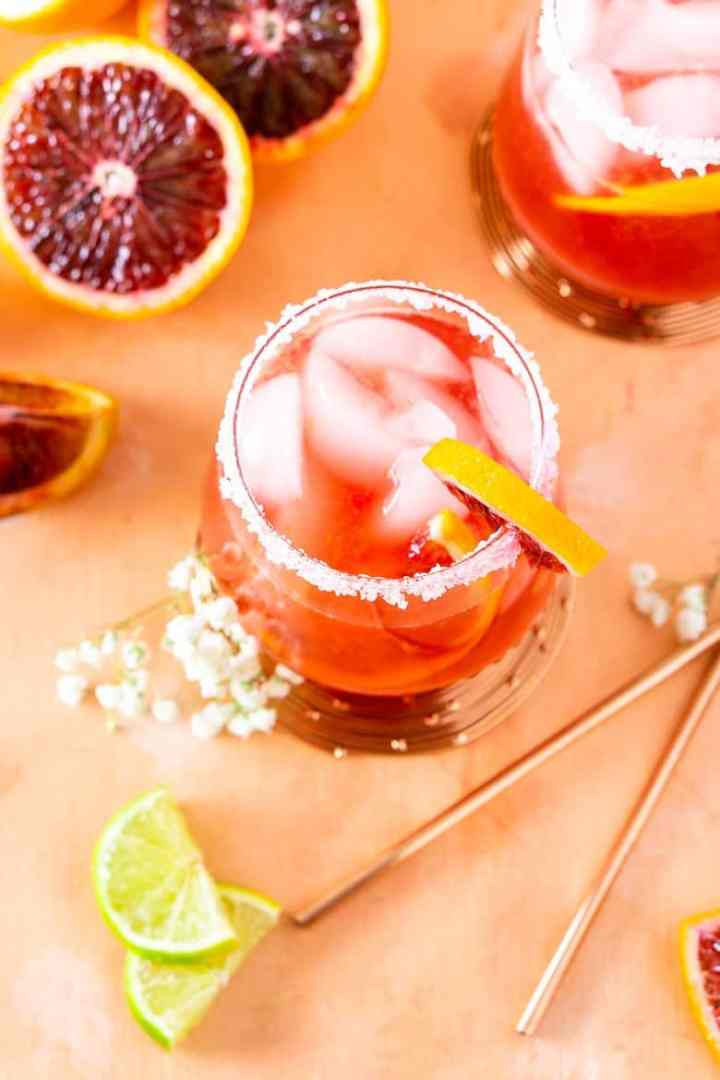 An aerial view of two blood orange margaritas with lime slices and straws.