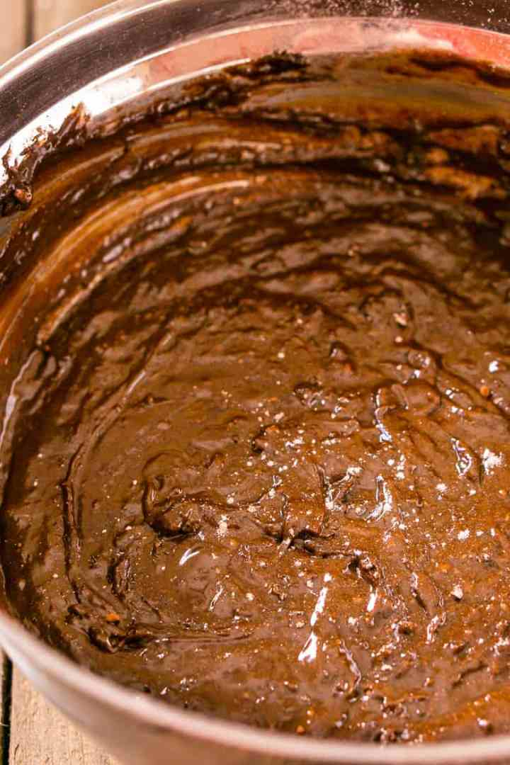 A bowl of fudgy stout brownie batter with just a few flour flakes on top.