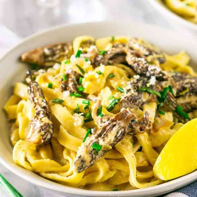A bowl of morel mushroom pasta with a blue and white napkin.