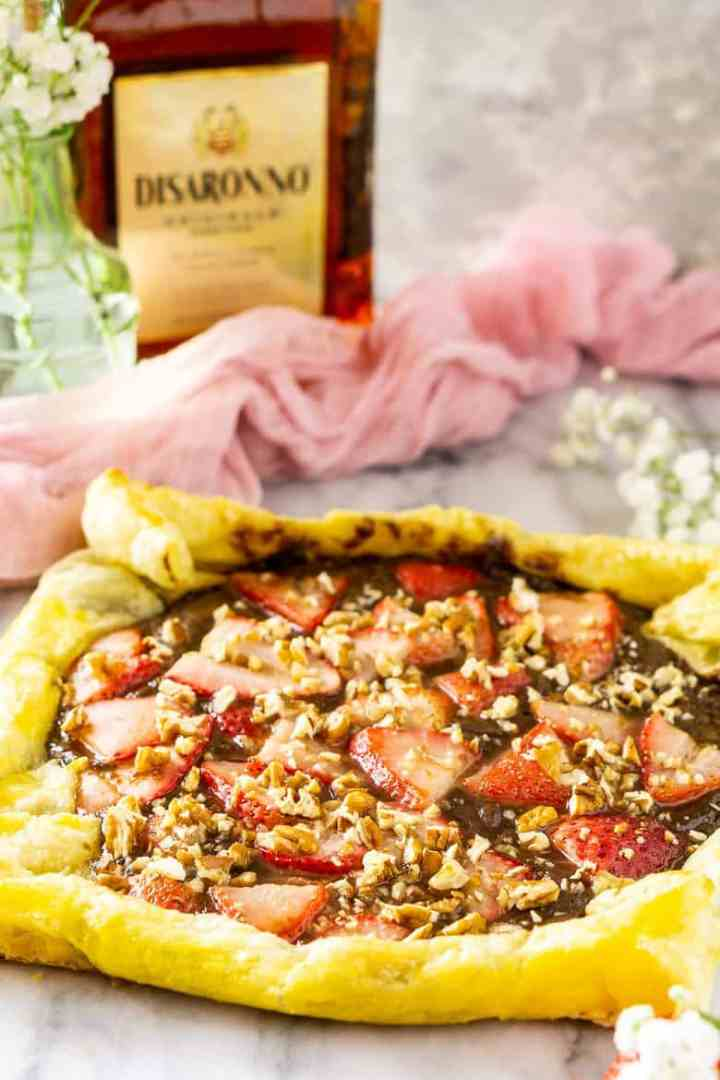 The amaretto strawberry Nutella puff pastry tart with flowers and a bottle of amaretto.