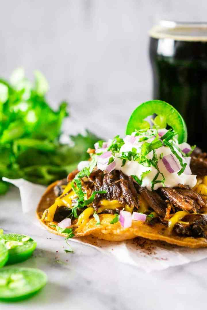 A tostada with beer-braised Mexican shredded beef with cilantro on the side.