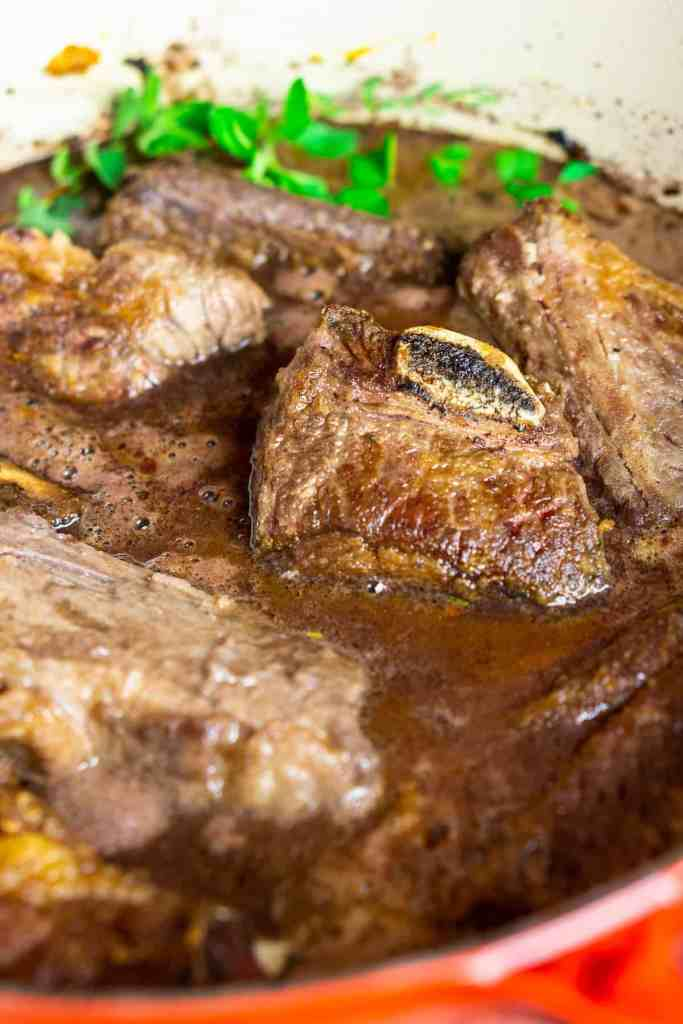 The browned short ribs are back in the Dutch oven with herbs and ready to braise.