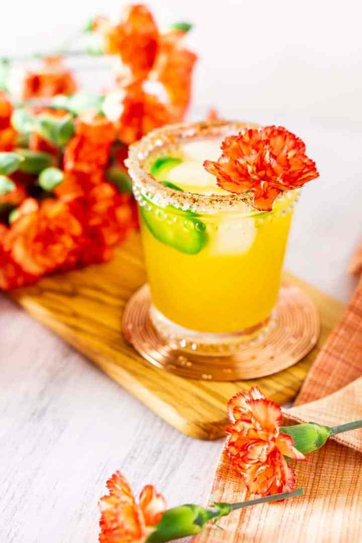 A jalapeno-mango margarita on a wooden board and copper coaster with flowers.