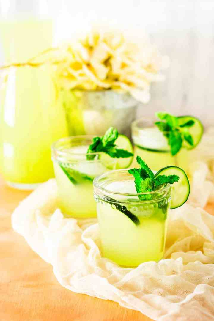 Three mint-cucumber lemonades on cheesecloth and a pink background.