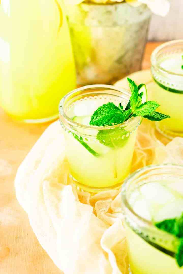 A glass of mint-cucumber lemonade with two other glasses in the foreground and background.
