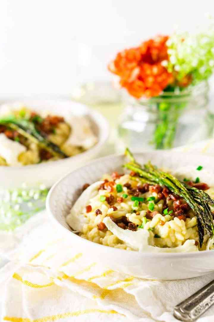 Two bowls of spring risotto with flowers in the background.