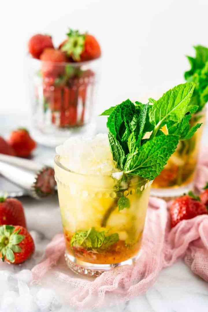 A glass of strawberry mint julep with another glass in the background.