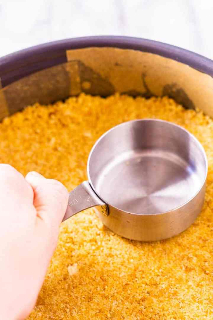 Using a measuring cup to press down the crumbs of the crust.