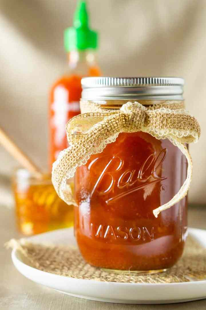 A close-up of a jar of honey-sriracha BBQ sauce with sriracha and honey in the background.