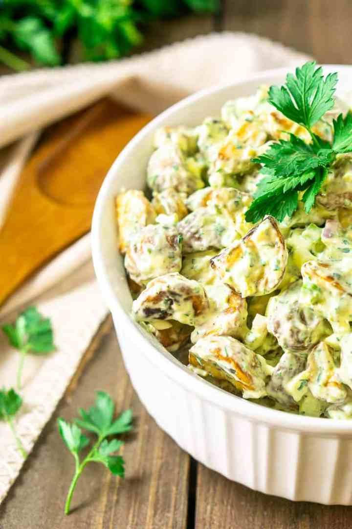 A bowl of herbed roasted potato salad with a serving spoon.