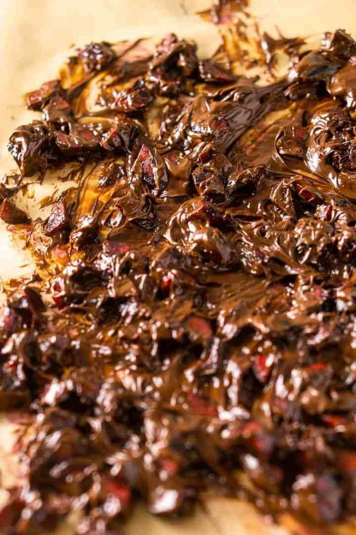 Chopped cherries covered in melted chocolate on brown parchment paper for the chocolate-covered cherry cheesecake.