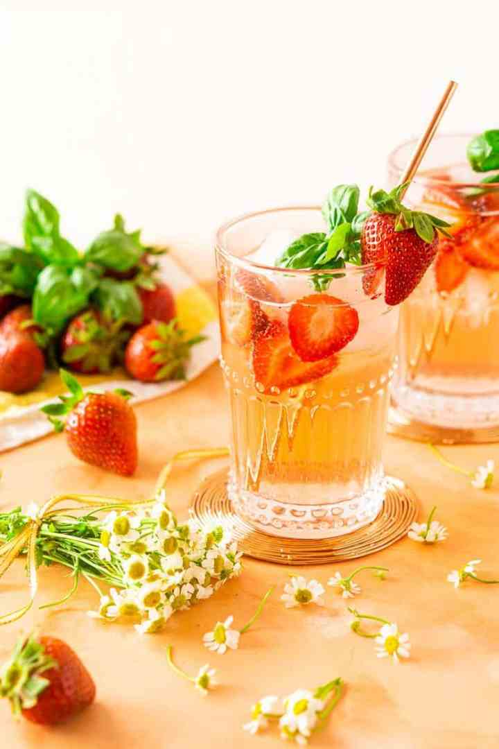 Two strawberry-basil Tom Collins drinks with flowers and strawberries.