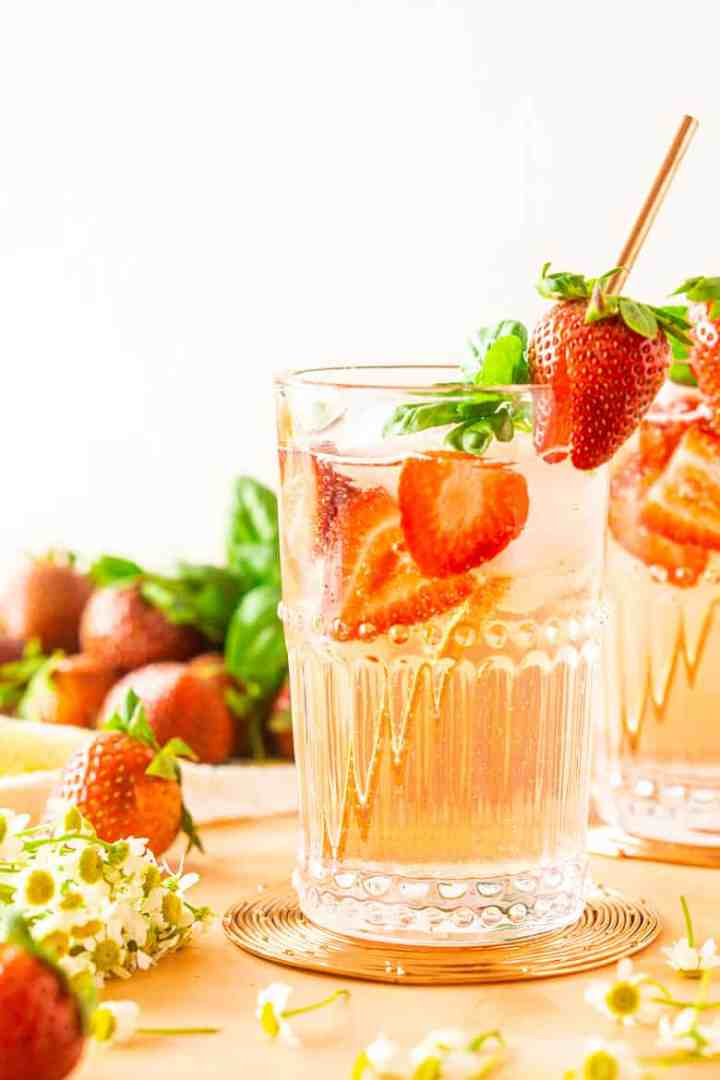 A close-up of a strawberry-basil Tom Collins with strawberries beside it.
