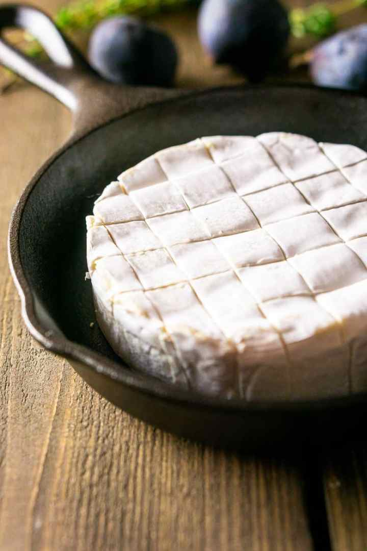 A round of Brie cut into cubes and placed in a small cast-iron skillet.