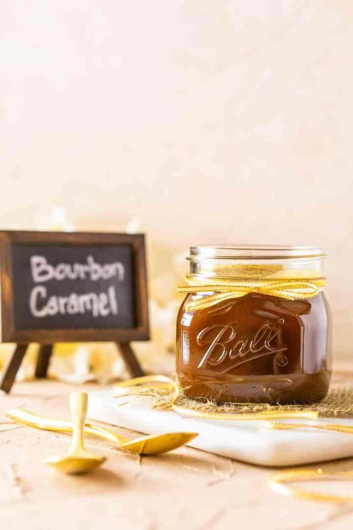 A jar of bourbon caramel sauce with a gold ribbon on a marble tray.