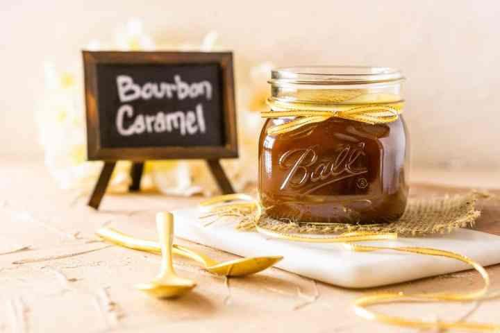 A jar of bourbon caramel sauce with two spoons and the chalkboard sign.