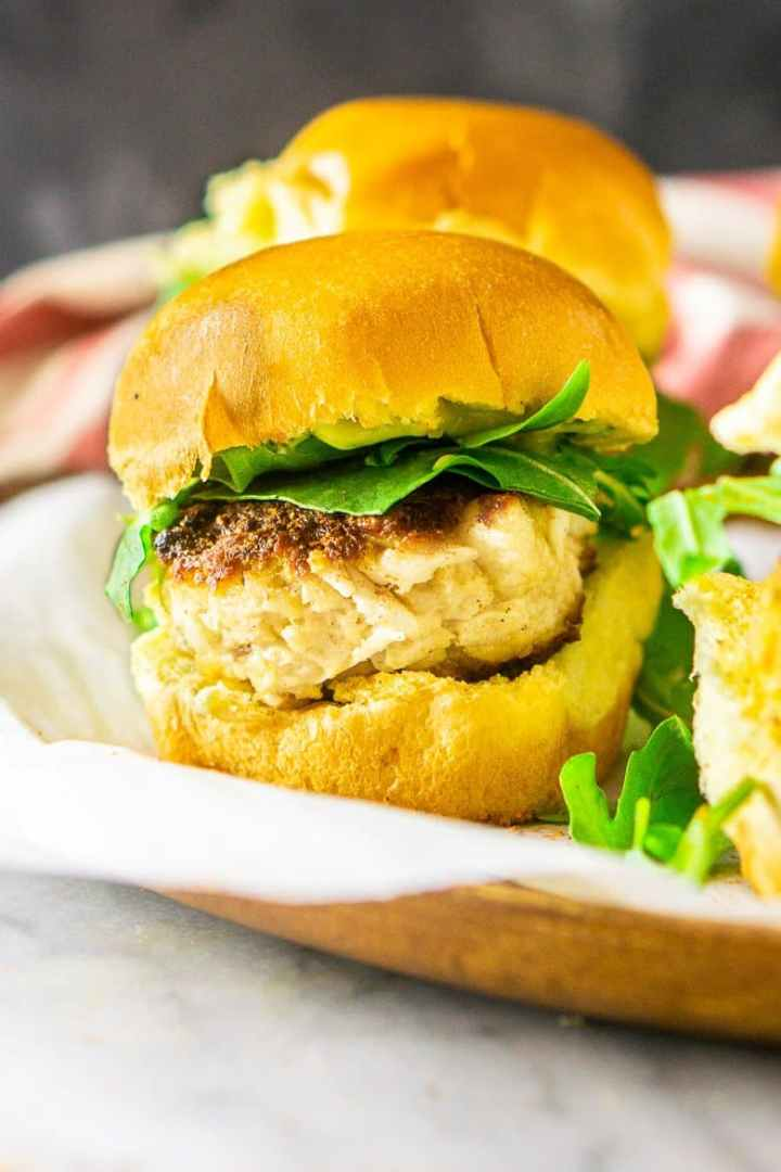 A close-up of a single crab cake slider on a tray.