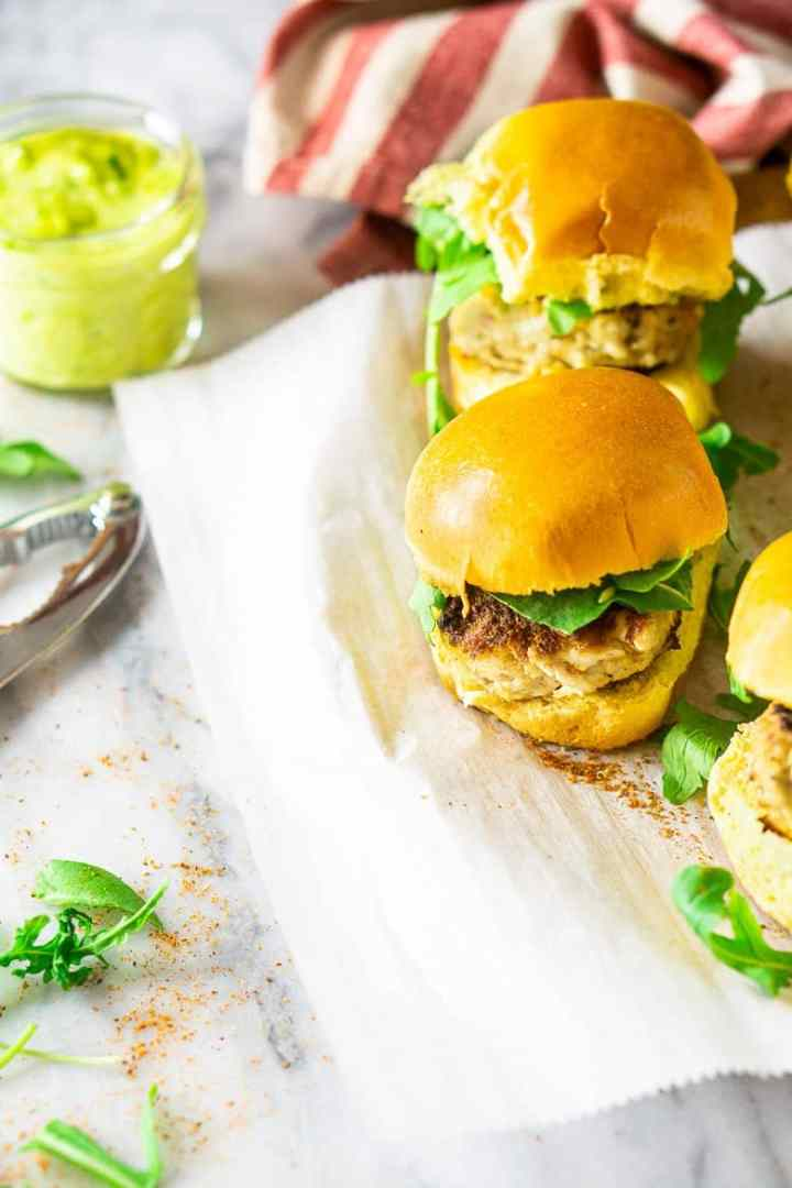 Looking down on a tray of crab cake sliders with a jar of basil-avocado aioli.