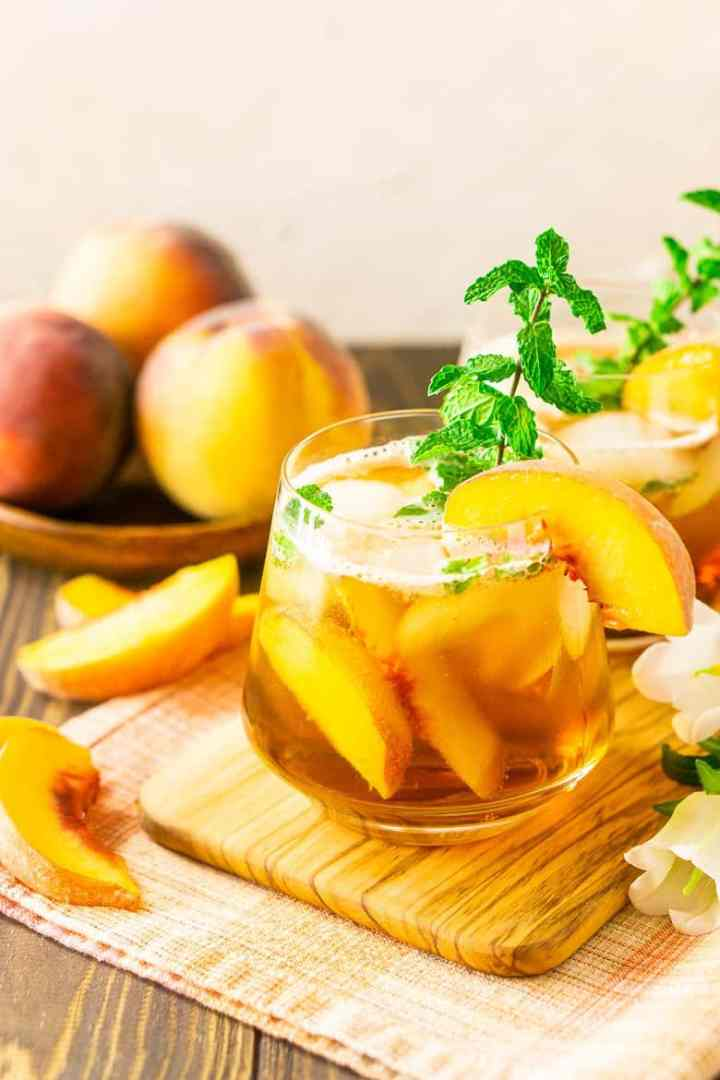 A peach-maple bourbon smash with flowers and peach slices.