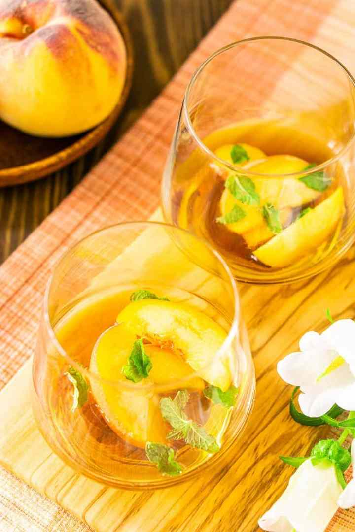 Slices of peaches, mint sprigs and maple syrup ready to muddle.