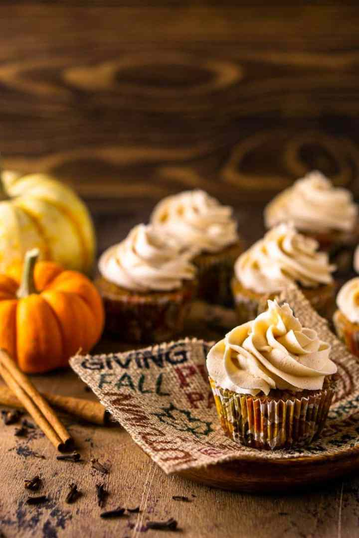 A brown butter pumpkin cupcake on a fall-themed piece of burlap with pumpkins, cinnamon sticks and other cupcakes in the background.