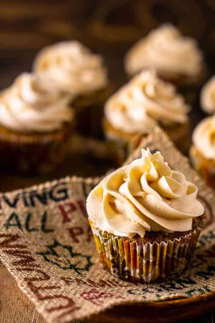 A close-up of a brown butter pumpkin cupcake on burlap and a wooden plate.