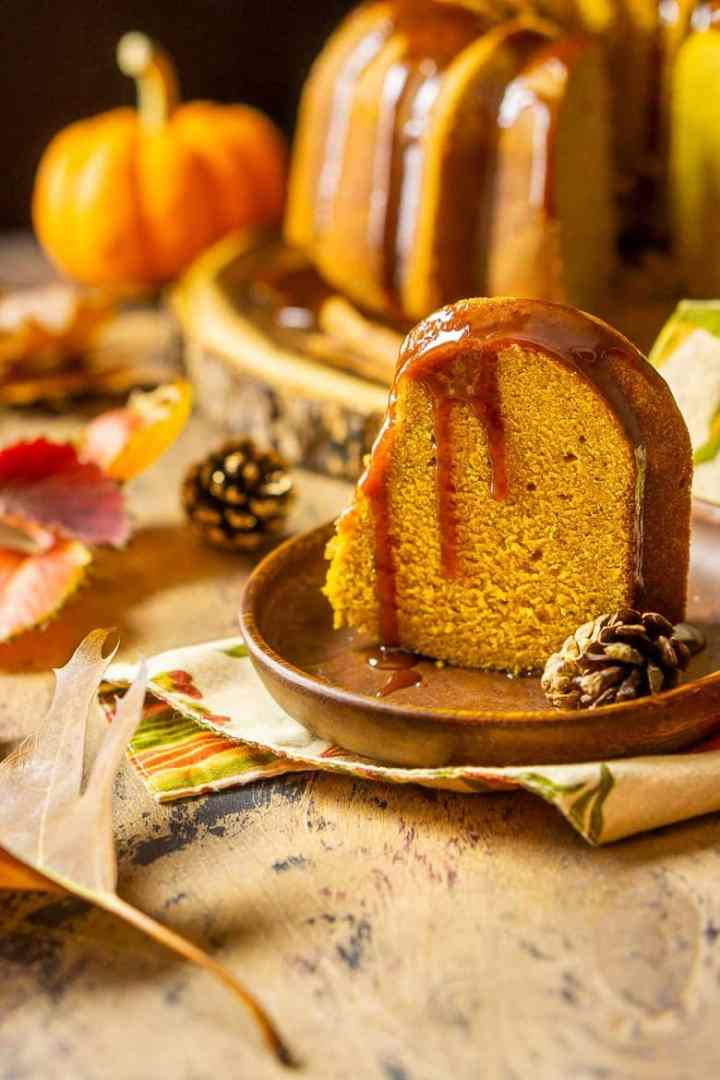 A slice of buttermilk-pumpkin pound cake on a wooden plate with the rest of the cake in the background.