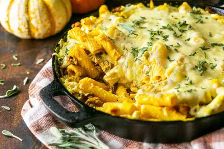 A skillet of chorizo and pumpkin baked ziti with a pumpkin in the background.