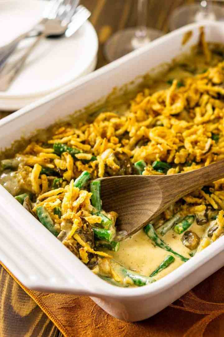 A baking dish of homemade green bean casserole with a wooden serving spoon inside.