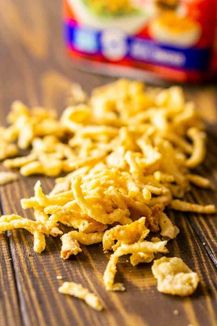 A pile of French's Crispy Fried Onions for the homemade green bean casserole on a wooden board.