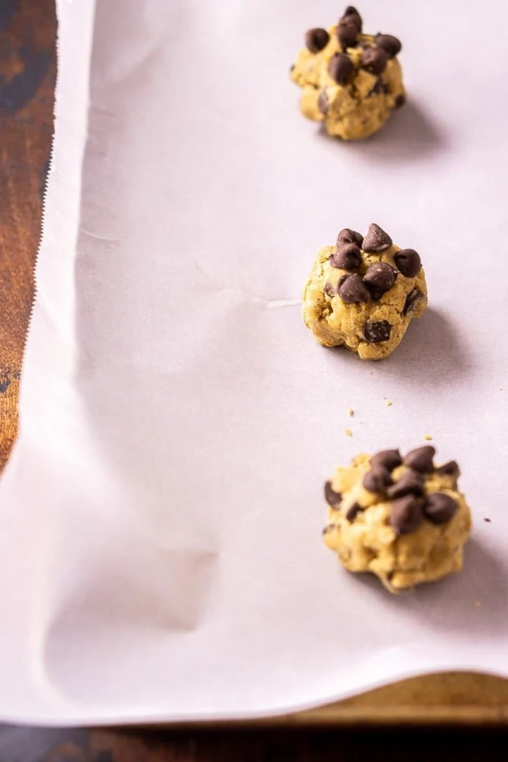 A baking sheet with three balls of cookie dough.