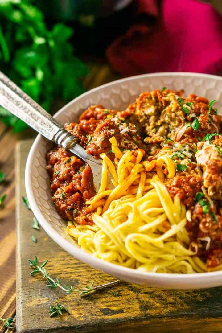 A fork twirled in a bowl of spaghetti and Italian meatballs on a wooden tray.