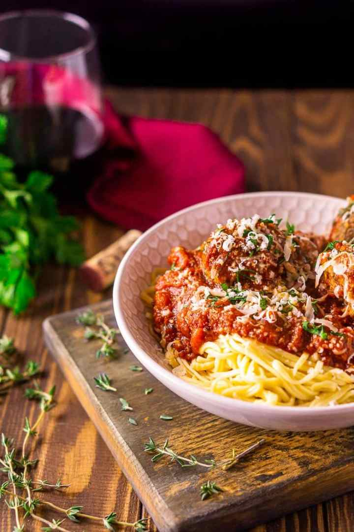 A bowl of Italian meatballs and spaghetti with a glass of wine and burgundy napkin in the background along with fresh herbs.